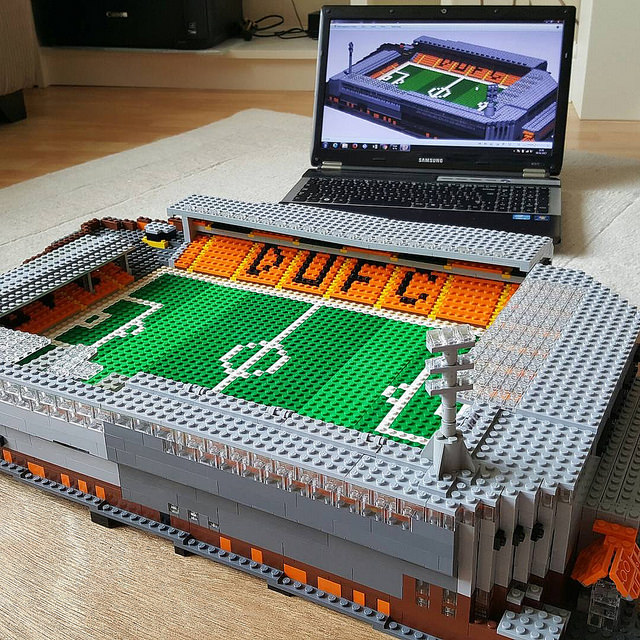 Lego football stadium model infront of laptop showing computer model of football stadium